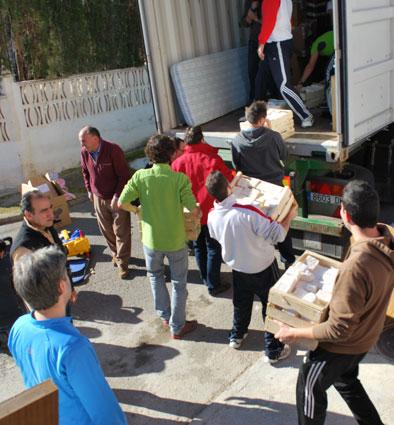 Los voluntarios cargan las cajas con jabón casero