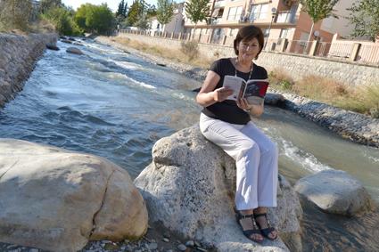 Teresa Ariza posa con su poemario, en las orillas del río Genil